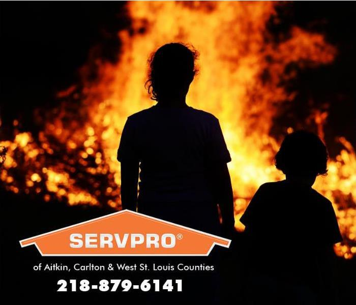 Two children are silhouetted against the backdrop of a structure fire blazing in the distance at night.